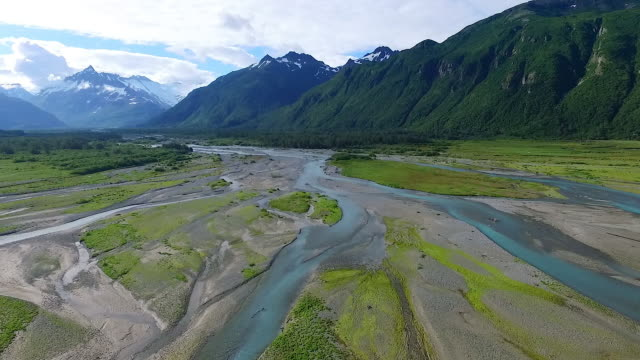 Aerial view flying forward up braided river mouth towards mountains