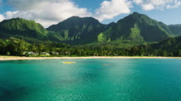 Aerial view flying over hawaiian canoes towards beautiful green mountains and