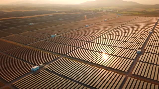 luftaufnahme über solarpark bei sonnenuntergang - fuel and power generation stock-videos und b-roll-filmmaterial