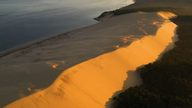 aerial view flying over the surrounding forest that borders the dune of pilat, europe's tallest sand dune. - sand dune stock videos & royalty-free footage