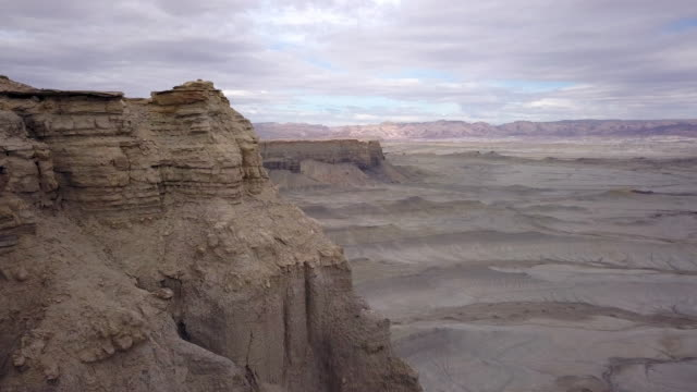 Aerial view flying past cliff viewing the terrain across the desert