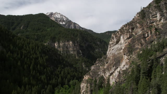 aerial view flying past rocky cliff in a canyon. - american fork city stock videos & royalty-free footage