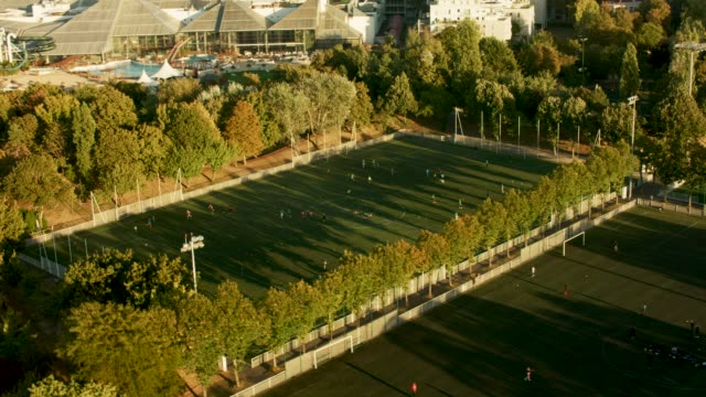 aerial view flying past soccer fields with people playing in paris france, daytime - football pitch stock videos & royalty-free footage