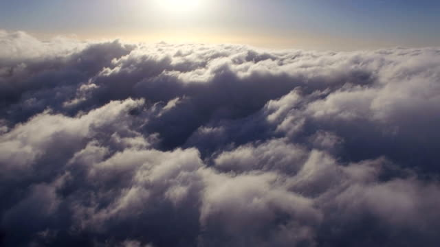 aerial view -flying through white clouds against blue sky with sunrise - paranormale video stock e b–roll