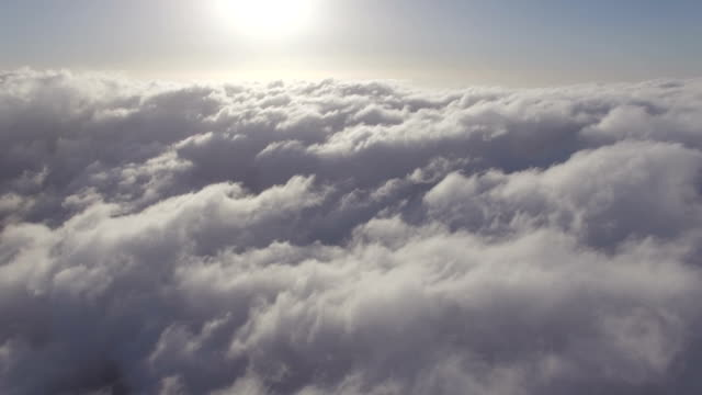 aerial view -flying through white clouds against blue sky with sunrise - atmospheric mood stock videos & royalty-free footage
