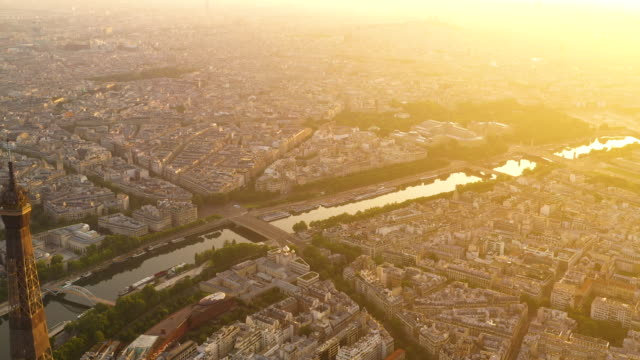vidéos et rushes de aerial view flying towards and past the eiffel tower in paris france at sunrise - wide shot