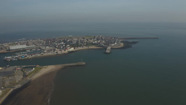aerial view flying towards the headland from hartlepool over sea - jetty stock videos & royalty-free footage