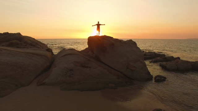 aerial view, flyover of silhouette man in the top of rock with the arms raised at sunset in the beach - cádiz stock videos and b-roll footage