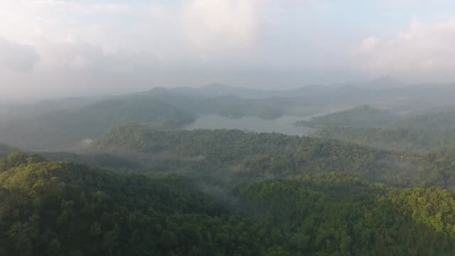 Aerial view fog sits in a valley near the Kalibiru Tourism Village in this aerial video taken at Kulon Progo Regency Special Region of Yogyakarta...