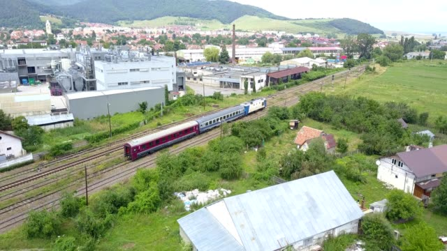 Aerial view following a commuter train leaving Codlea railway station in Brasov County Romania