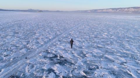 vídeos de stock e filmes b-roll de aerial view following a man walking on the frozen baikal lake, russia - ártico