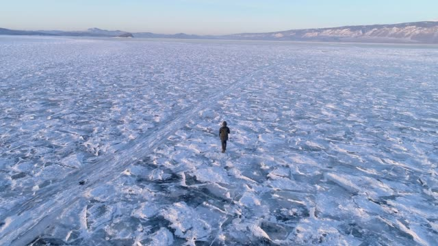 stockvideo's en b-roll-footage met aerial view following a man walking on the frozen baikal lake, russia - arctis