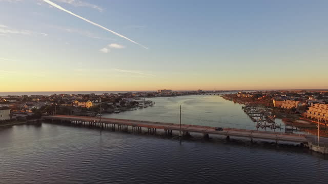 drone. aerial view following car heading to luxury beach houses during spectacular sunrise at wrightsville beach - louisiana stock videos & royalty-free footage