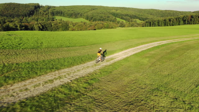 vidéos et rushes de 4k aerial view following woman on mountain bike in hilly landscape - route à une voie