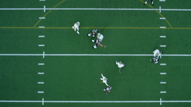ws aerial view  football punt returner receiving punt and returning ball down field - アメリカンフットボール場点の映像素材/bロール