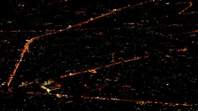 Luftbild vom Flugzeug aus dem Fenster mit beleuchteten Stadtbild bei Nacht.