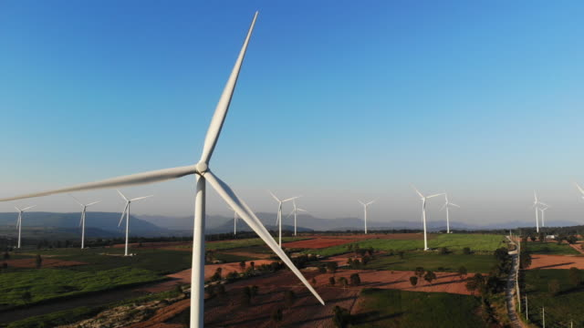 Aerial view from drone horizontal axis wind turbine with blue sky.