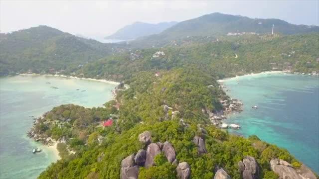 海やビーチ、澄んだ青い海の水海の上の驚くべき低空中ショット以上コー タオ島タイ便で岩のドローンから空撮。 - 夏休み点の映像素材/bロール