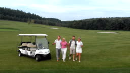 Aerial view from drone. Two couples getting ready to play. A group of smiling friends came to the hole on a golf cart