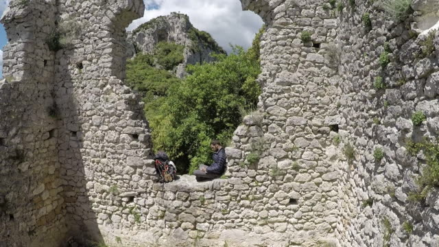 aerial view from hiker sitting on stone wall to hills, forest - stone wall stock videos and b-roll footage