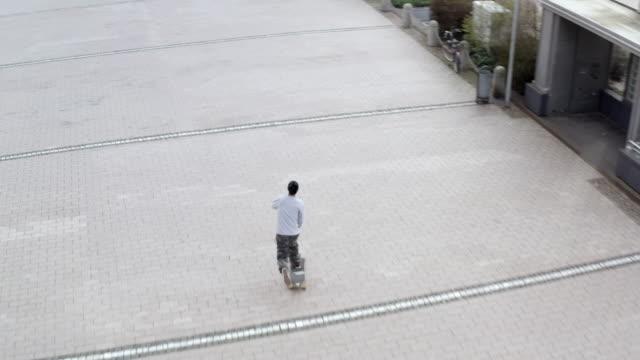 aerial view from man riding a skateboard - 全身点の映像素材/bロール
