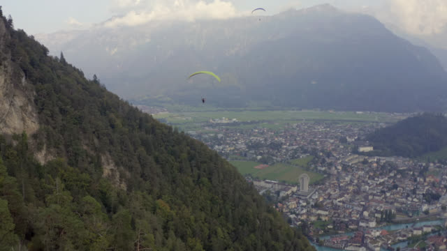 aerial view from paragliding flying above interlaken in swiss alps - パラグライディング点の映像素材/bロール