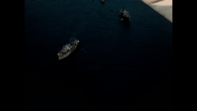 Aerial view from plane as it flies over Tokyo Harbor revealing US Navy supply ships for the fleet