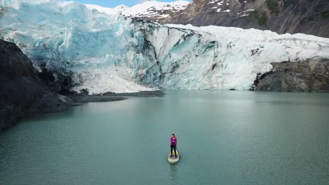 stockvideo's en b-roll-footage met aerial view glacier & woman paddling away from it - baai
