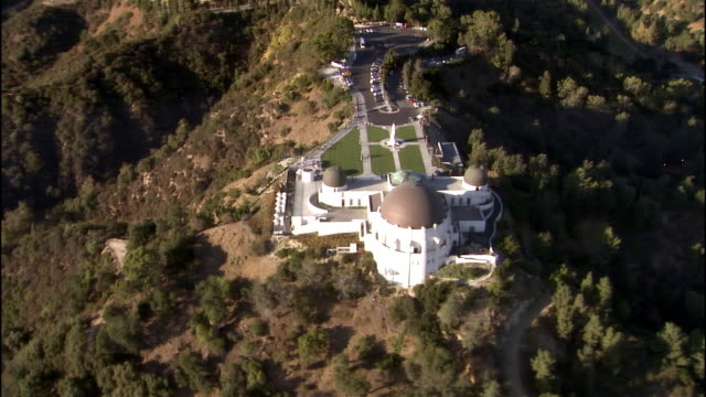 aerial view griffith observatory / pan downtown cityscape in distance / los angeles, california - griffith observatory stock videos & royalty-free footage