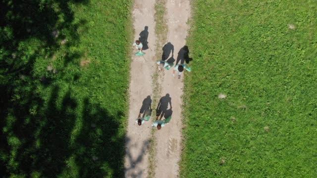 航空写真 - 森林の谷を歩くゴミ袋を持つボランティアのグループ - ボランティア点の映像素材/bロール