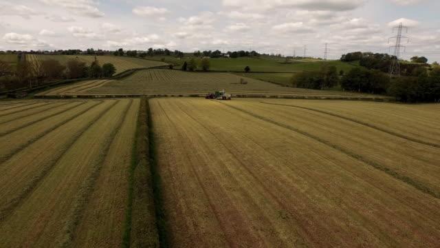 aerial view harvester & tractor working in field - traktor stock-videos und b-roll-filmmaterial