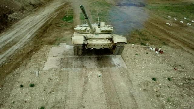 vidéos et rushes de vue aérienne - le char lourd surmonte la barrière verticale sur la course d'obstacles - char véhicule blindé