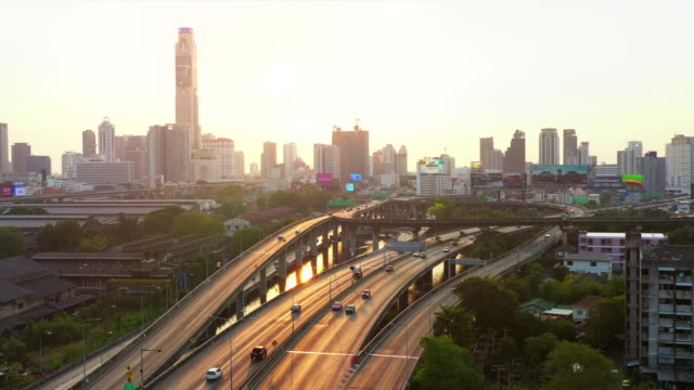 aerial view highway with city at sunset - american interstate stock videos & royalty-free footage