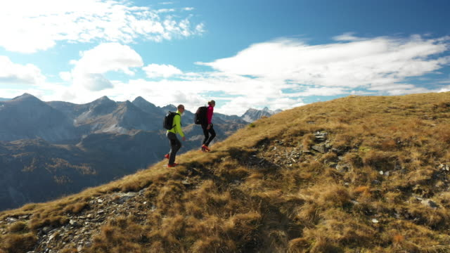 4k aerial view hiking couple on ridge mountain panorama autumn - österreich stock-videos und b-roll-filmmaterial