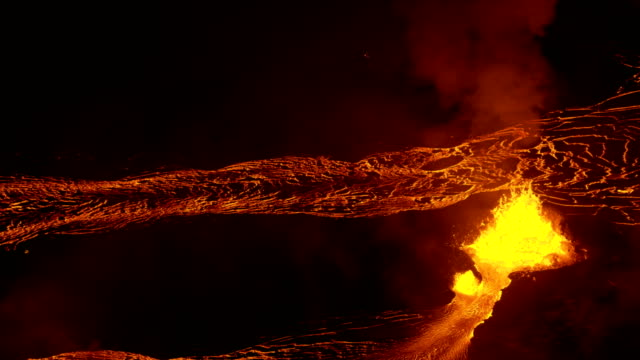 aerial view hot lava pouring from open fissure - lava stock-videos und b-roll-filmmaterial