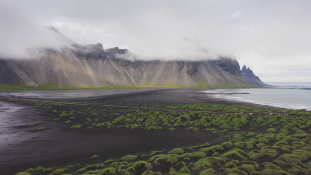 4k aerial view hyper lapse of black lava beach, mount vestrahorn, stokksnes, eastern region, iceland - moss stock videos & royalty-free footage