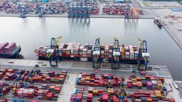 vídeos de stock e filmes b-roll de aerial view hyperlapse timelapse of international port with crane loading containers in import export business logistics. - cadeia de lojas