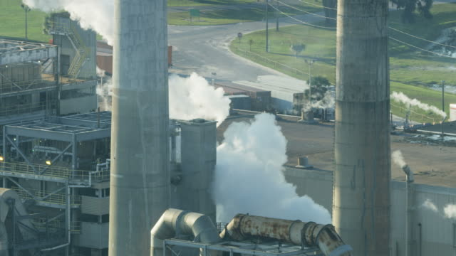 vídeos de stock e filmes b-roll de aerial view industrial plant towers extracting smoke emissions - gas station
