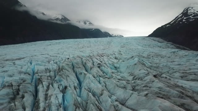 Aerial View Jagged Glacier Ice Between Mountains