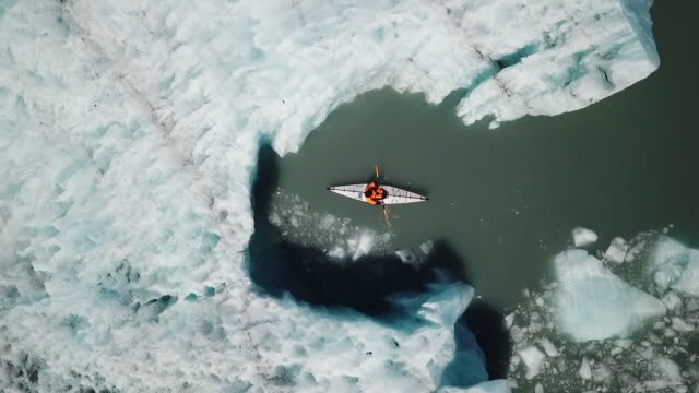 Aerial View Kayaker Back-Paddling next to Iceberg