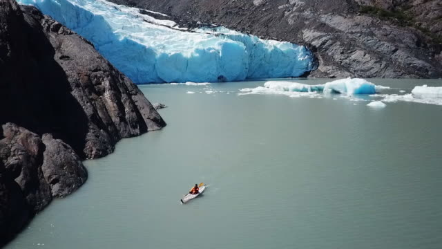 stockvideo's en b-roll-footage met aerial view kayaker paddling away from glacier - baai