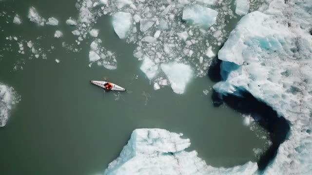 Aerial View Kayaker Paddling Away from Iceberg