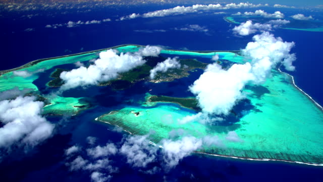 aerial view lagoon and island of bora bora - isola di tahaa video stock e b–roll