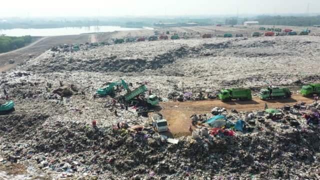 aerial view landfill with garbage trucks unloading - destruction stock videos & royalty-free footage