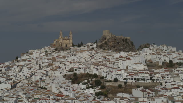 aerial view leaving castle and church in cityscape on hill / olvera, malaga, spain - cádiz stock videos and b-roll footage