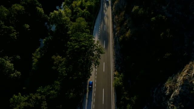 Aerial View looking down on Highway Cutting Through Forest