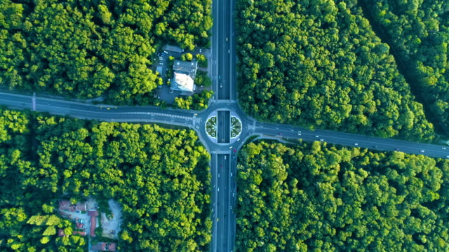 aerial view looking down on traffic circle in the middle of a beautiful forest slow motion 48fps - dolly shot stock videos & royalty-free footage