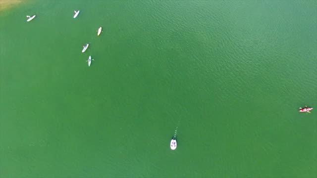 stockvideo's en b-roll-footage met luchtfoto uitzicht op zoek recht naar beneden op kayakers en stand up paddle boarders op stad lake austin texas - sunshine lake