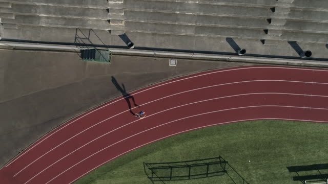 uhd 4k aerial view: male sprinter training and sprinting on a track - pista di atletica leggera video stock e b–roll
