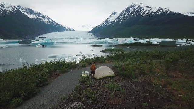 aerial view man camping near glacier in alaska - campeggiare video stock e b–roll